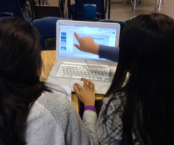 Two girls researching online using a Chromebook laptop.