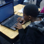 Student focused on his laptop learning to program instruction for the Hydrodynamics lego robot.