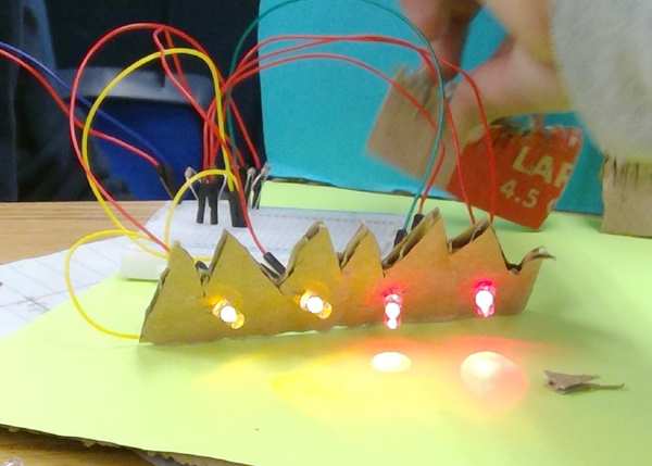 A close up of wiring up LED lights to a protoboard to light them.